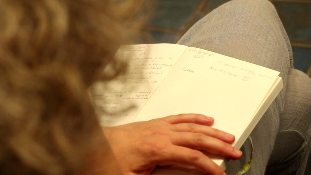 Plan d'une main sur un carnet par dessus une épaule